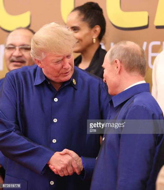 US President Donald Trump shakes hands with Russia's President Vladimir Putin as they pose for a group photo ahead of the AsiaPacific Economic...