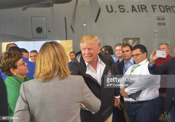 US President Donald Trump shakes hands with San Juan Mayor Carmen Yulín Cruz during briefing on Hurricane Maria relief efforts at a hanger at Luis...