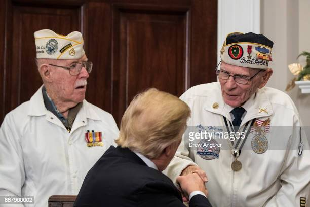 President Donald Trump shakes hands with survivors of the 1941 attack on Pearl Harbor after signing a proclamation for National Pearl Harbor...