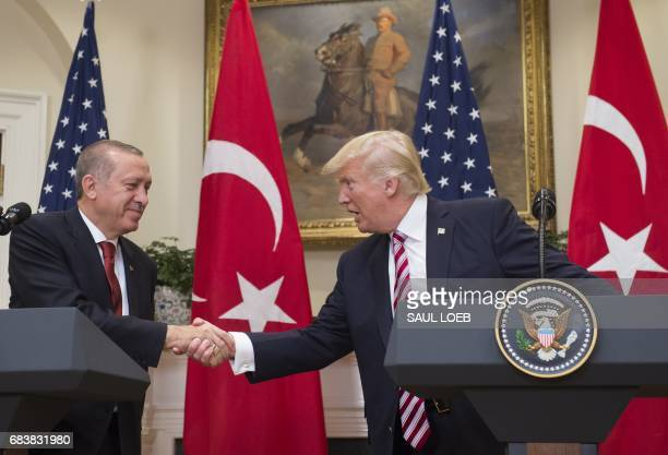 US President Donald Trump shakes hands with Turkish President Recep Tayyip Erdogan after speaking to the press in the Roosevelt Room of the White...