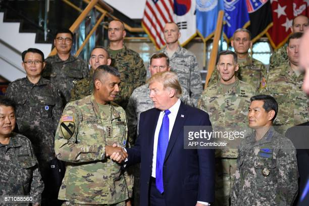 US President Donald Trump shakes hands with US Forces Korea Commander General Vincent Brooks at the 8th Army Operational Command Centre at Camp...