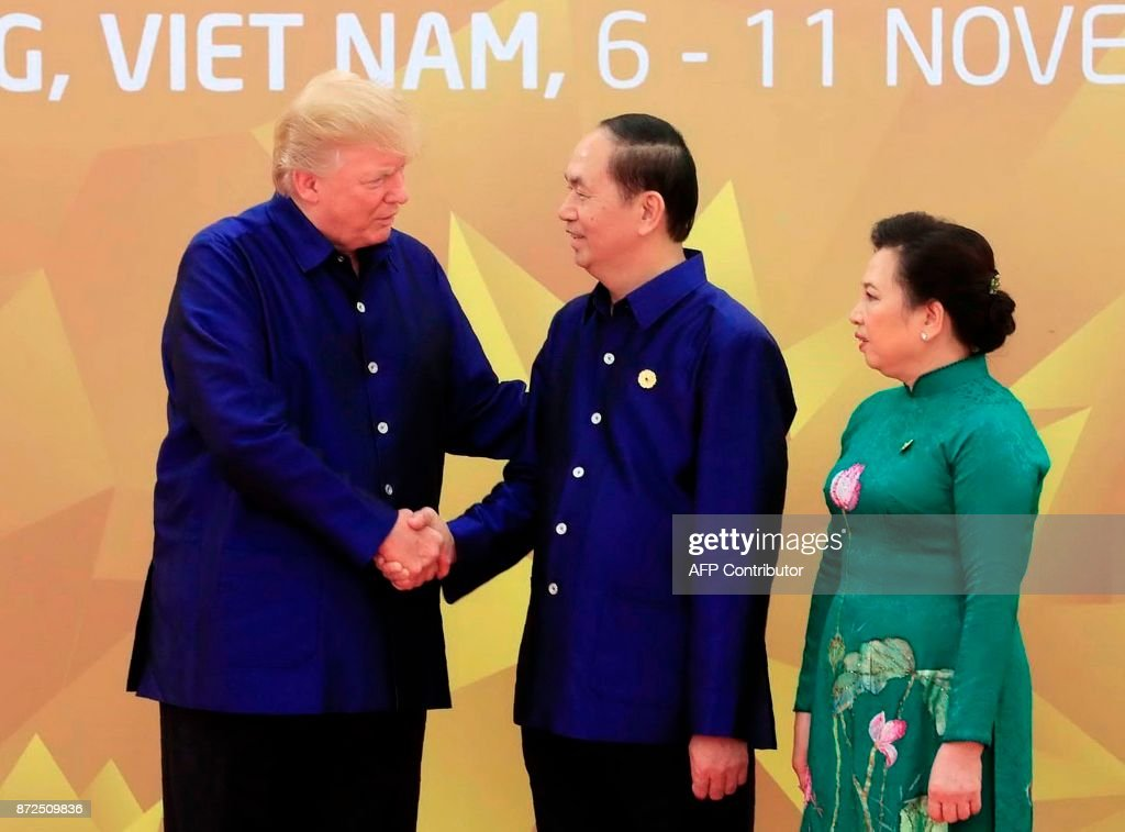 US President Donald Trump (L) shakes hands with Vietnams President Tran Dai Quang as his wife Nguy?n Th? Hi?n (R) looks on, upon arrival for the Asia-Pacific Economic Cooperation (APEC) Summit leaders gala dinner in the central Vietnamese city of Danang on November 10, 2017. World leaders and senior business figures are gathering in the Vietnamese city of Danang this week for the annual 21-member APEC summit. / AFP PHOTO / Vietnam News Agency / STR