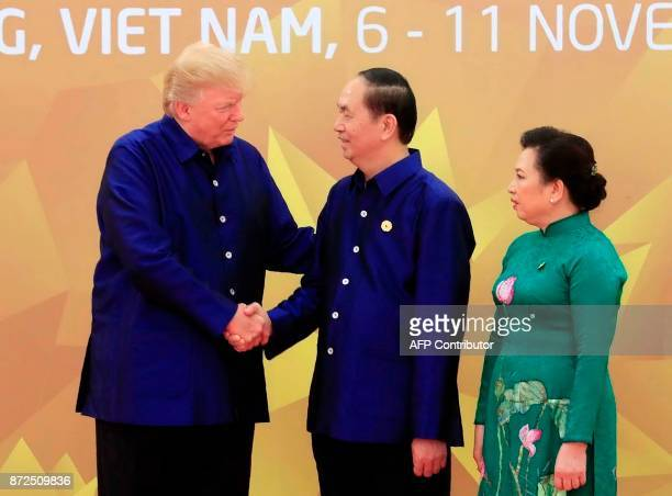 US President Donald Trump shakes hands with Vietnams President Tran Dai Quang as his wife Nguyn Th Hin looks on upon arrival for the AsiaPacific...