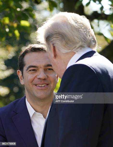 US President Donald Trump shakes hands with with Greece's Prime Minister Alexis Tsipras following their joint press conference in the Rose Garden of...