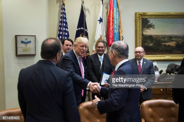 President Donald Trump shakes the hand of EPA Administrator Scott Pruitt as he arrives to speak during an energy roundtable with tribal state and...