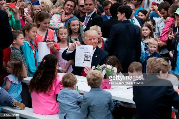 US President Donald Trump shows a note he wrote while writing to service members with children during the Easter Egg Roll on the South Lawn of the...