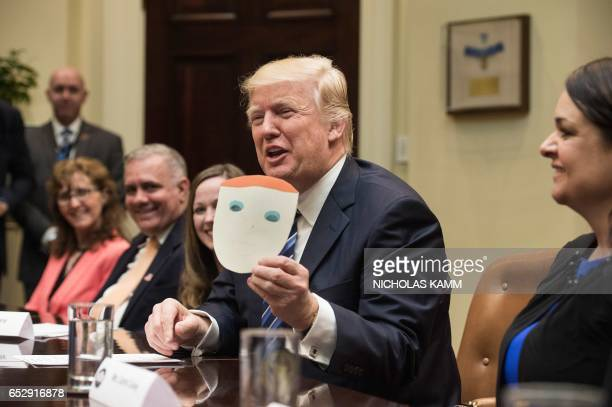 US President Donald Trump shows a picture of himself made by the son of participant Greg Brown during a meeting about healthcare in the Roosevelt...