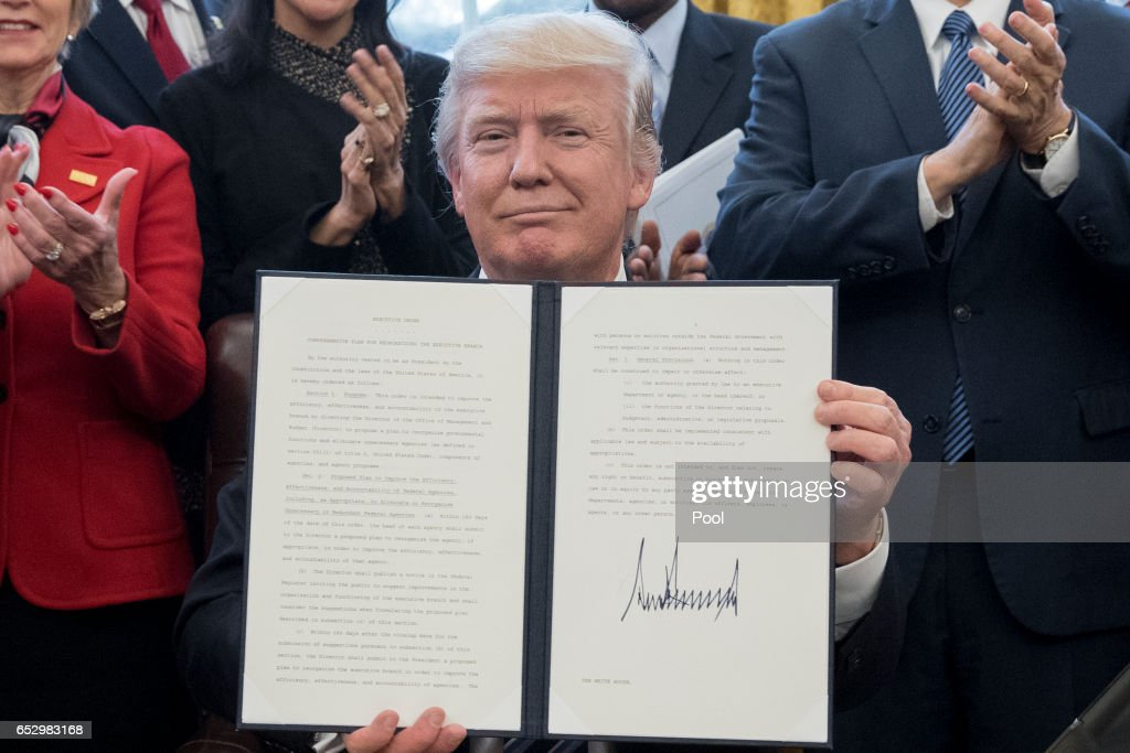President Donald Trump shows an executive order entitled, 'Comprehensive Plan for Reorganizing the Executive Branch', after signing it beside members of his cabinet in the Oval Office of the White House on March 13, 2017 in Washington, DC.