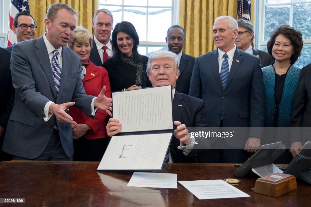 President Donald Trump shows an executive order entitled, 'Comprehensive Plan for Reorganizing the Executive Branch', after signing it beside members of his Cabinet in the Oval Office of the White House March 13, 2017 in Washington, DC. Also pictured are Director of the Office of Management and Budget (OMB) Mick Mulvaney (Front L), Treasury Secretary Steven Mnuchin (Back L), Administrator of the Small Business Administration Linda McMahon (2-L), Secretary of the Interior Ryan Zinke (3-L), US Ambassador to the UN Nikki Haley (4-L), Secretary of Housing and Urban Developement (HUD) Ben Carson (Back C), US Vice President Mike Pence (2-R) and Secretary of Transportation Elaine Chao (R).