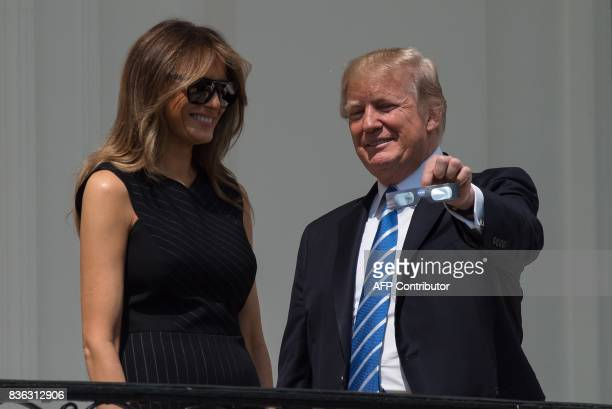 US President Donald Trump shows his eclipse glasses First Lady Melania Trump from the balcony of the White House during the partial solar eclipse in...