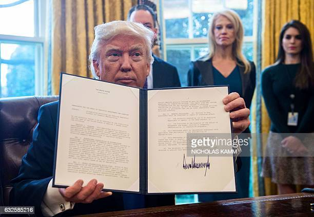 US President Donald Trump shows one of the executive orders he signed in the Oval Office at the White House in Washington DC on January 24 2017 US...