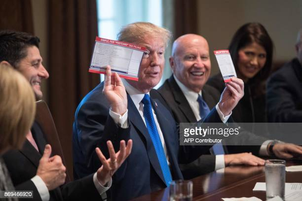 US President Donald Trump shows samples of the proposed new tax form as he meets with House Republican leaders and Republican members of the House...