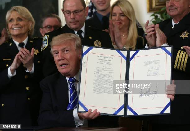 S President Donald Trump shows the bill he has signed during a bill signing in the Diplomatic Reception Room of the White House June 2 2017 in...