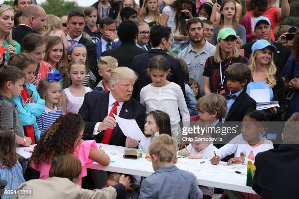 S President Donald Trump shows the coloring sheet he wrote on to children he joined at a craft table during the 139th Easter Egg Roll on the South...