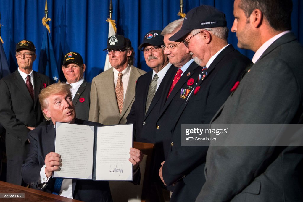 US President Donald Trump signs a proclamation in commemoration of the 50th anniversary of the Vietnam War on the sidelines of the Asia-Pacific Economic Cooperation (APEC) leaders' summit in the central Vietnamese city of Danang on November 10, 2017. World leaders and senior business figures are gathering in the Vietnamese city of Danang this week for the annual 21-member APEC summit. /