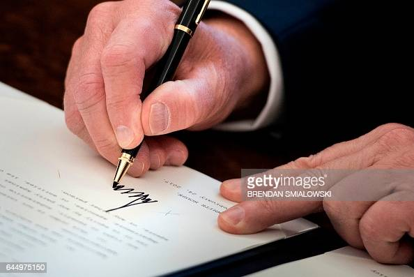 US President Donald Trump signs an executive order about regulatory reform in the Oval Office of the White House February 24 2017 in Washington DC /...