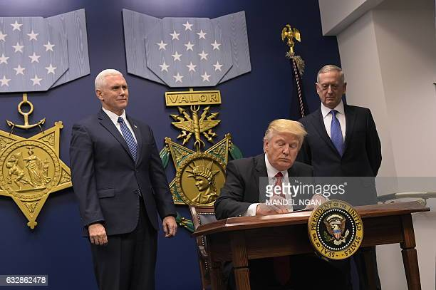 US President Donald Trump signs an executive order alongside US Defense Secretary James Mattis and US Vice President Muike Pence on January 27 at the...