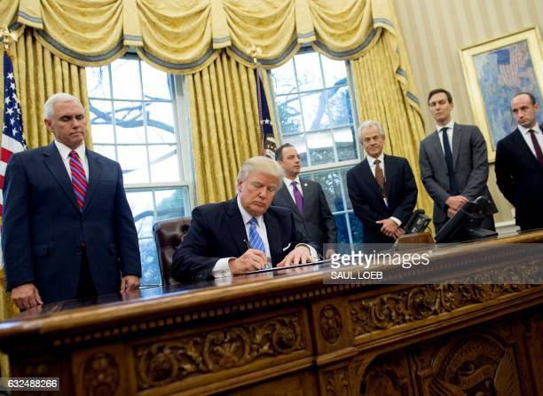 President Donald Trump signs an executive order alongside White House Chief of Staff Reince Priebus US Vice President Mike Pence National Trade...