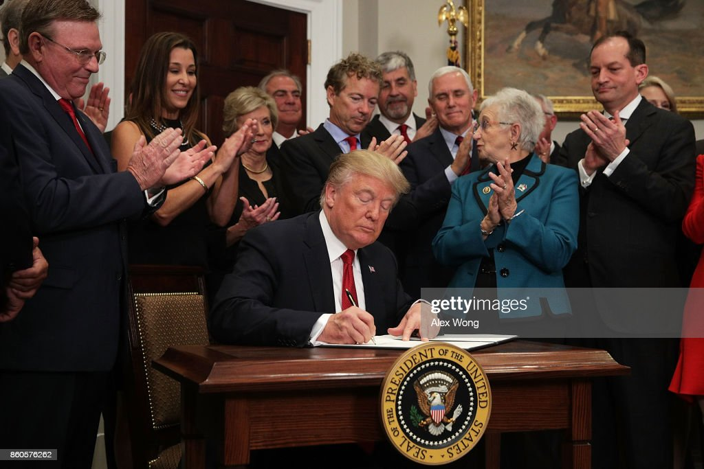 U.S. President Donald Trump signs an executive order as Sen. Rand Paul (R-KY), Vice President Mike Pence, Rep. Virginia Foxx (R-NC) and Secretary of Labor Alexander Acosta look on during an event in the Roosevelt Room of the White House October 12, 2017 in Washington, DC. President Trump signed the executive order to loosen restrictions on Affordable Care Act 'to promote healthcare choice and competition.'