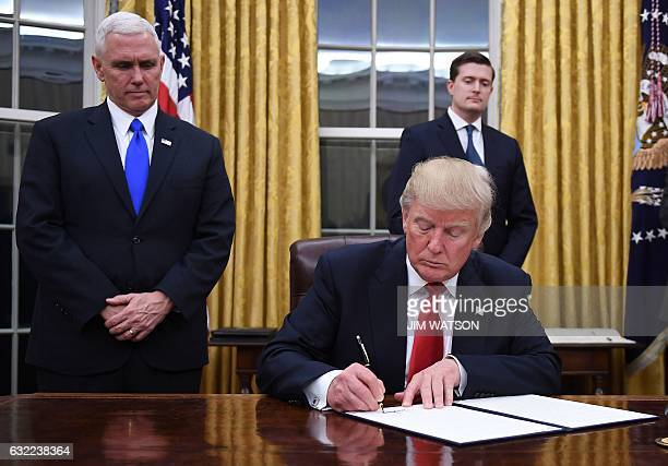 US President Donald Trump signs an executive order as Vice President Mike Pence looks on at the White House in Washington DC on January 20 2017 / AFP...