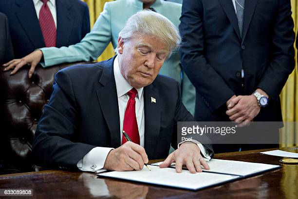 US President Donald Trump signs an executive order in the Oval Office of the White House surrounded by small business leaders January 30 2017 in...