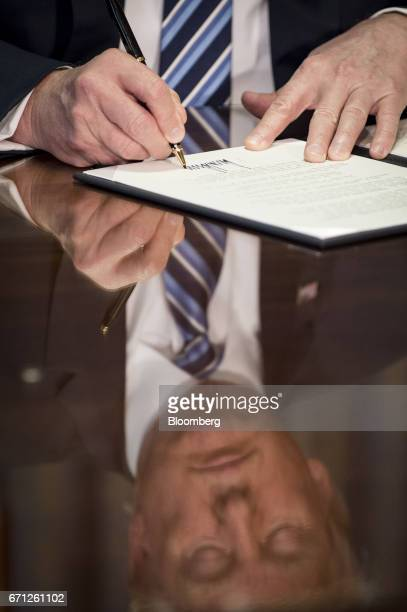 US President Donald Trump signs an executive order in Washington DC US on Friday April 21 2017 The tax code became too expensive and burdensome under...