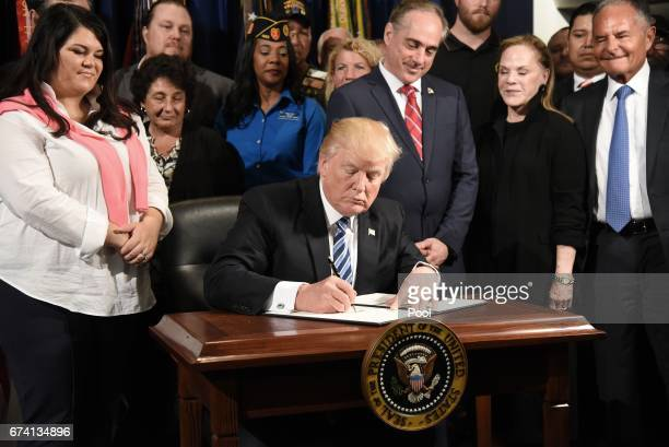 US President Donald Trump signs an Executive Order on Improving Accountability and Whistleblower Protection at the Department of Veterans Affairs on...