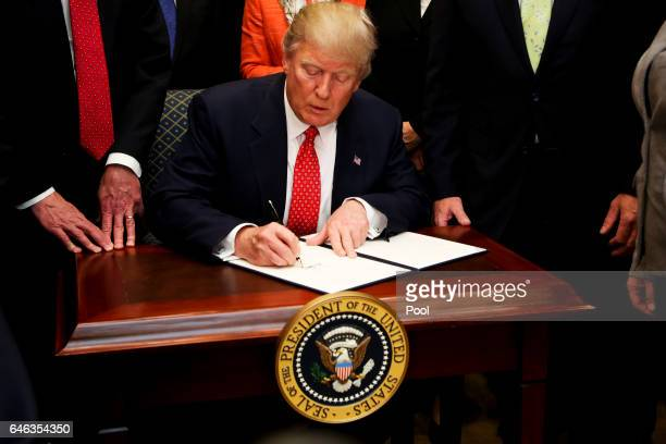 President Donald Trump signs an Executive Order to begin the rollback of environmental regulations put in place by the Obama administration February...