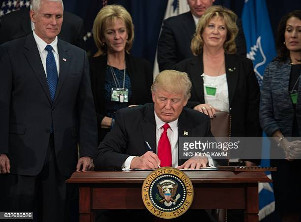 US President Donald Trump signs an executive order to start the Mexico border wall project at the Department of Homeland Security facility in...