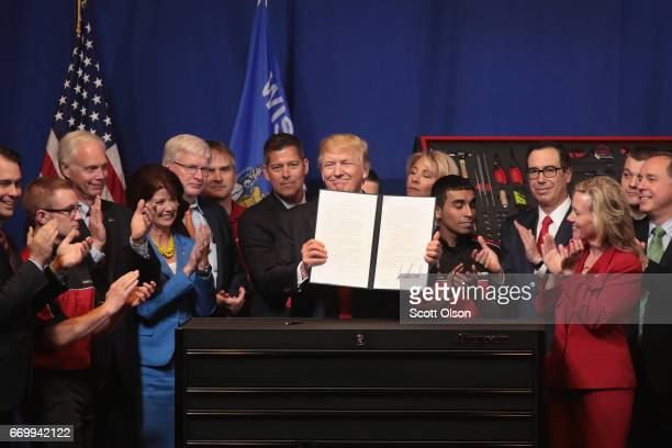 President Donald Trump signs an executive order to try to bring jobs back to American workers and revamp the H1B visa guest worker program during a...