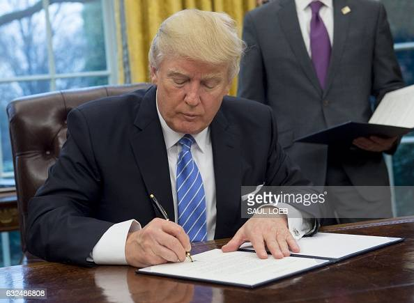 President Donald Trump signs an executive order withdrawing the US from the TransPacific Partnership in the Oval Office of the White House in...