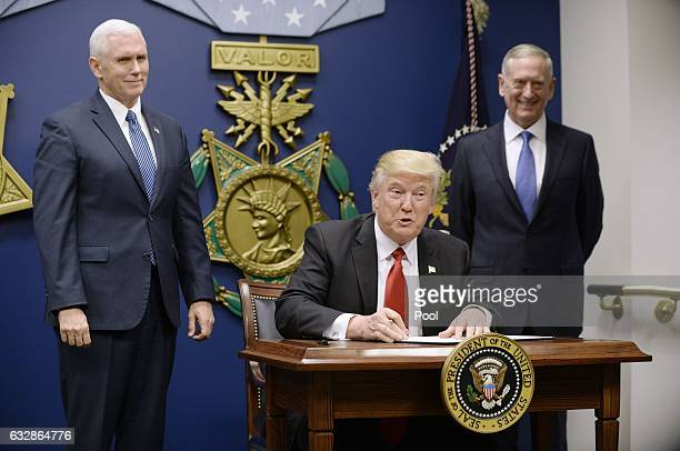 S President Donald Trump signs executive orders as Defense Secretary Gen James Mattis and Vice President Mike Pence look on in the Hall of Heroes at...