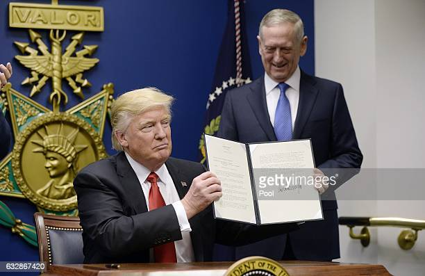 S President Donald Trump signs executive orders as Defense Secretary Gen James Mattis looks on in the Hall of Heroes at the Department of Defense on...