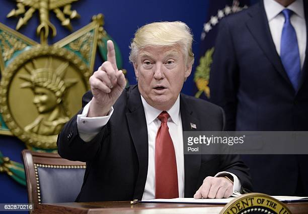 S President Donald Trump signs executive orders in the Hall of Heroes at the Department of Defense on January 27 2017 in Arlington Virginia Trump...