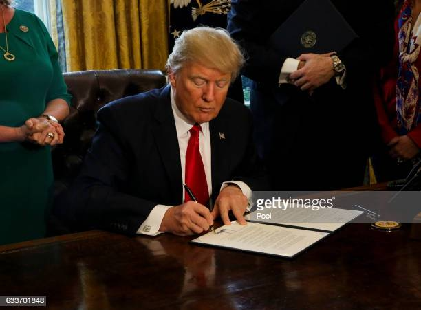 US President Donald Trump signs Executive Orders in the Oval Office of the White House including an order to review the DoddFrank Wall Street to roll...