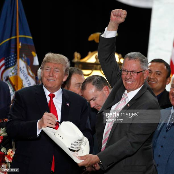 S President Donald Trump signs the cowboy hat of Bruce Adams Chairman of the San Juan County Commission at the Rotunda of the Utah State Capitol on...