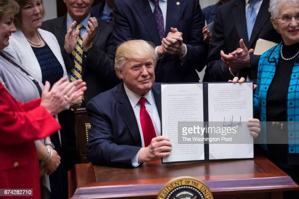 President Donald Trump signs the Education Federalism Executive Order during a federalism event with governors in the Roosevelt Room of the White...