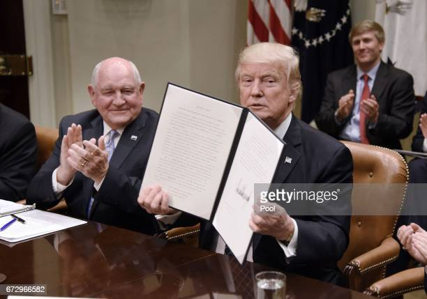US President Donald Trump signs the Executive Order Promoting Agriculture and Rural Prosperity in America as Agriculture Secretary Sonny Perdue looks...