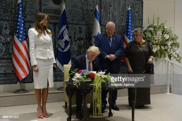 US President Donald Trump signs the guest book as his wife Melania Trump Israeli President Reuven Rivlin and his wife Nechama Rivlin stand next to...