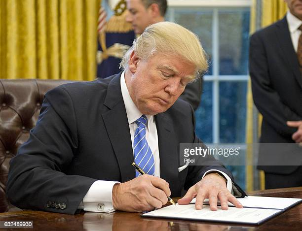 US President Donald Trump signs the last of three Executive Orders in the Oval Office of the White House in Washington DC on Monday January 23 2017...