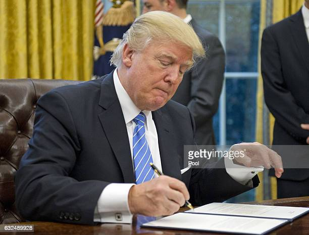 US President Donald Trump signs the second of three Executive Orders in the Oval Office of the White House in Washington DC on Monday January 23 2017...