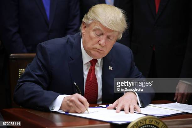 S President Donald Trump signs the Veterans Choice Program And Improvement Act in the Roosevelt Room at the White House April 19 2017 in Washington...