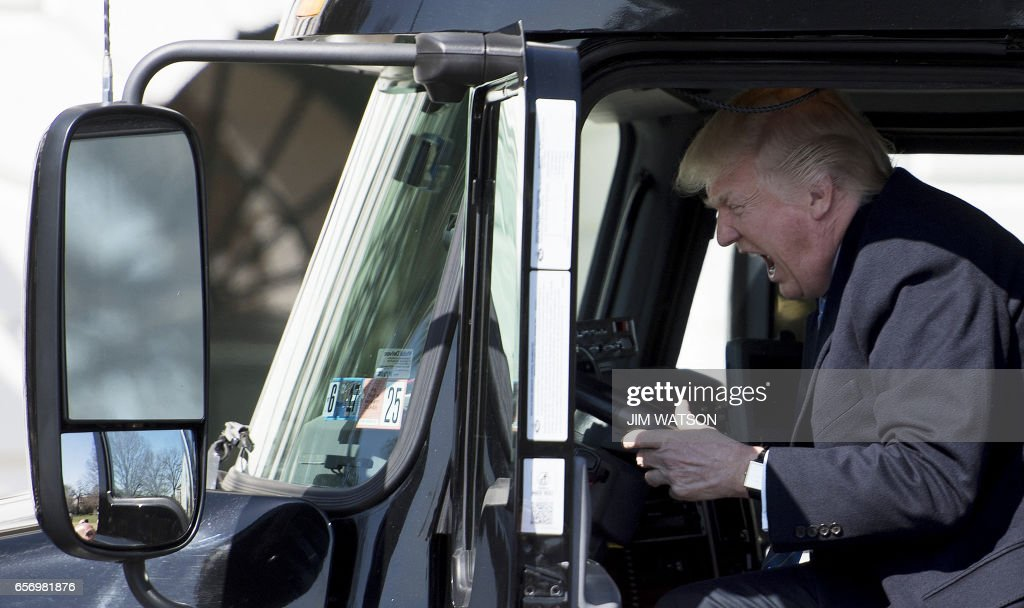 President Donald Trump sits in the drivers seat of a semi-truck as he welcomes truckers and CEOs to the White House in Washington, DC, March 23, 2017, to discuss healthcare. /