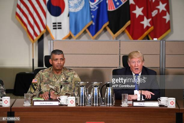 US President Donald Trump sits with US Forces Korea Commander General Vincent Brooks as he meets generals at the 8th Army Operational Command Centre...