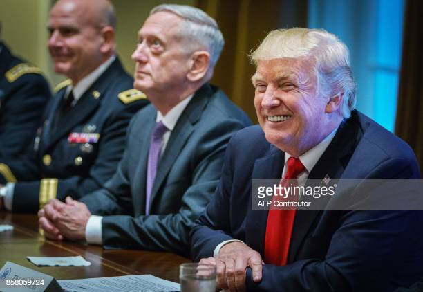 US President Donald Trump smiles as Defense Secretary James Mattis looks on during a meeting with senior military leaders in the Cabinet Room of the...