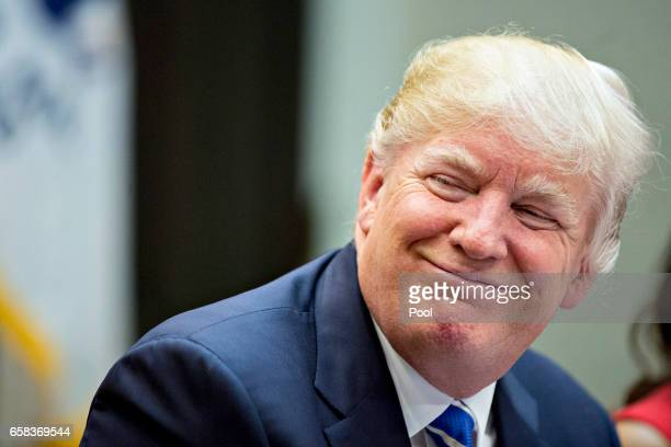 S President Donald Trump smiles while meeting with women small business owners in the Roosevelt Room of the White House on March 27 2017 in...