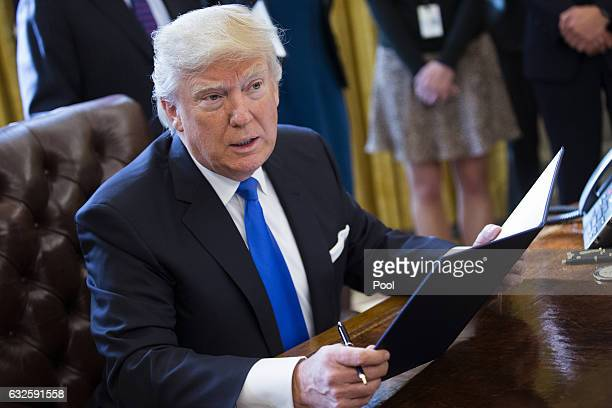 President Donald Trump speaks after signing executive orders related to the oil pipeline industry in the Oval Office of the White House January 24...