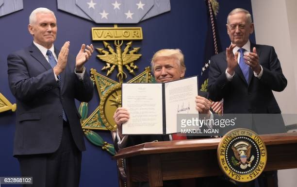 President Donald Trump speaks after signing executive orders alongside US Defense Secretary James Mattis and US Vice President Mike Pence on January...