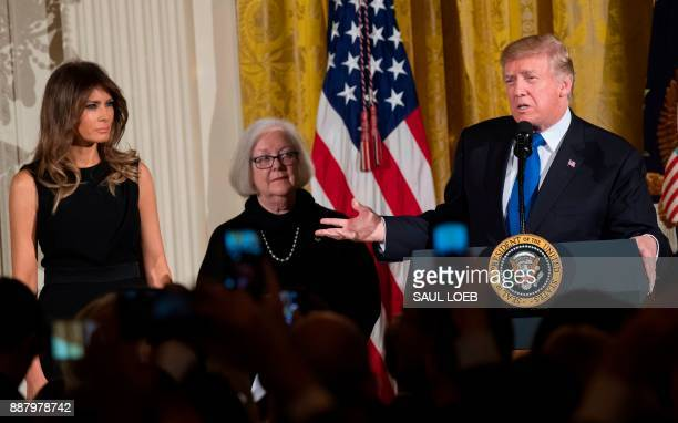 US President Donald Trump speaks alongside First Lady Melania Trump and Holocaust survivor Louise LawrenceIsraels during a Hanukkah reception in the...