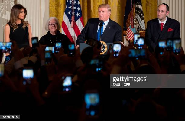US President Donald Trump speaks alongside First Lady Melania Trump Holocaust survivor Louise LawrenceIsraels and Rabbi Meir Soloveichik during a...
